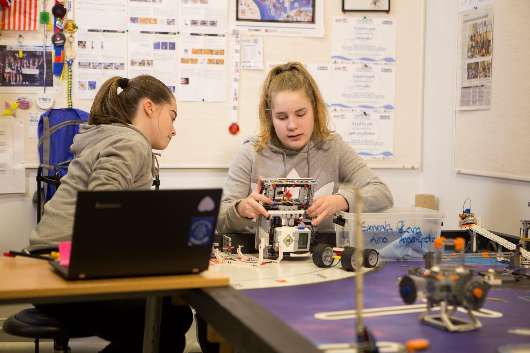 Kaksi koululaista rakentaa legorobottia.