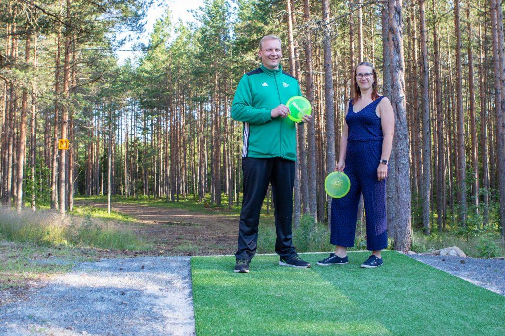 Vetofrisbeen vastaava Antti-Jussi Kivini ja Luvian vedon kuntojaoston puheenjohtaja Paula Haanpää seisovat uudella Luvian Vedon majan maastoon rakennetulla frisbeegolfkentällä.