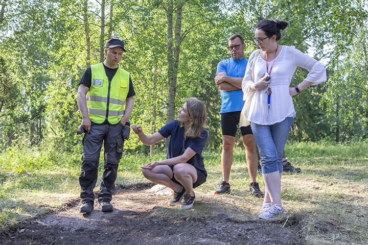 Ihmiset keskustelevat Liinmaan linnalla kaivauksista.