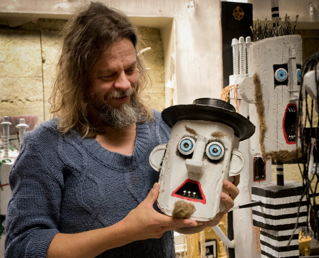 Vuoden 2021 ITE-taiteilija Jori Tapio Kalliola pitelee puupäistä ukkeliteostaan.
