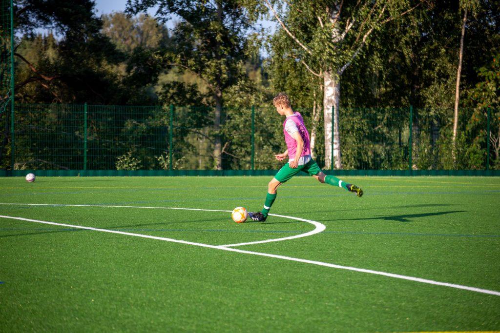 Jalkapalloilija potkaisee palloa tekonurmella